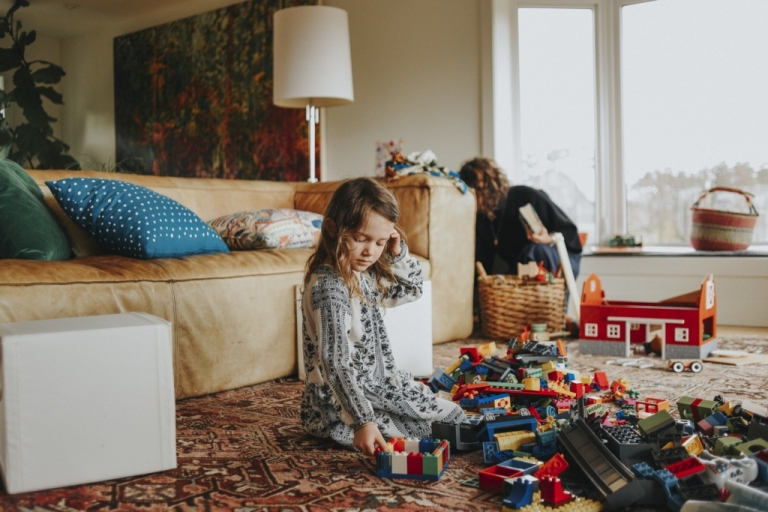 Girl sitting in house, playing with lego