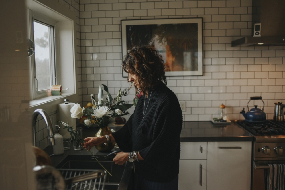 woman in kitchen, cutting flowers.