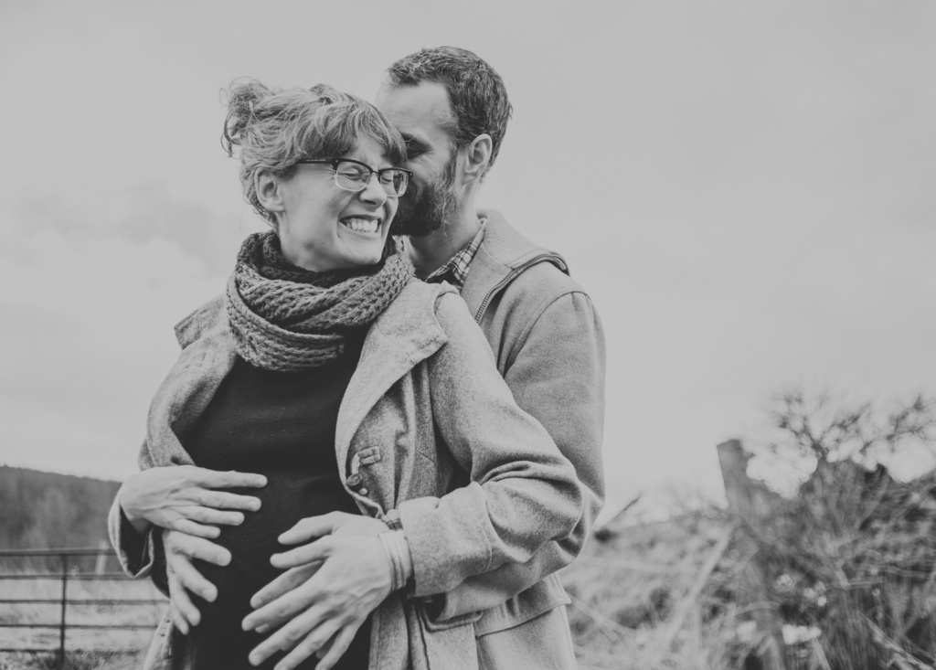 Man and woman, embracing and holding pregnant belly in a field.