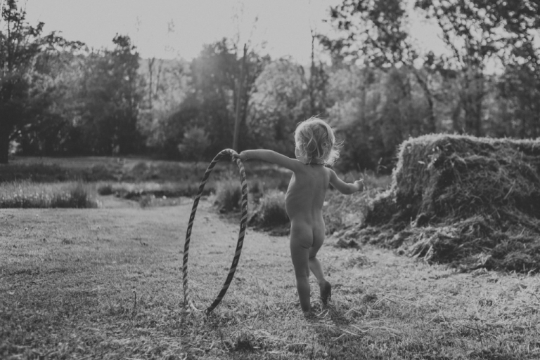 Toddler playing with hoola-hoop in yard.
