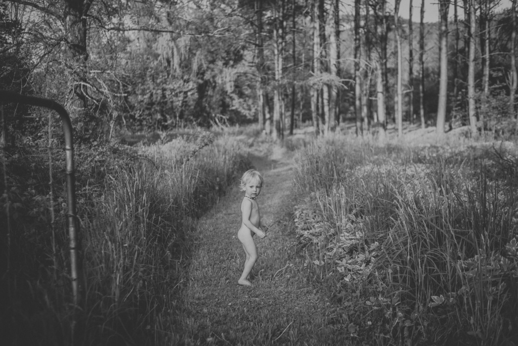 Toddler standing on wooded path.