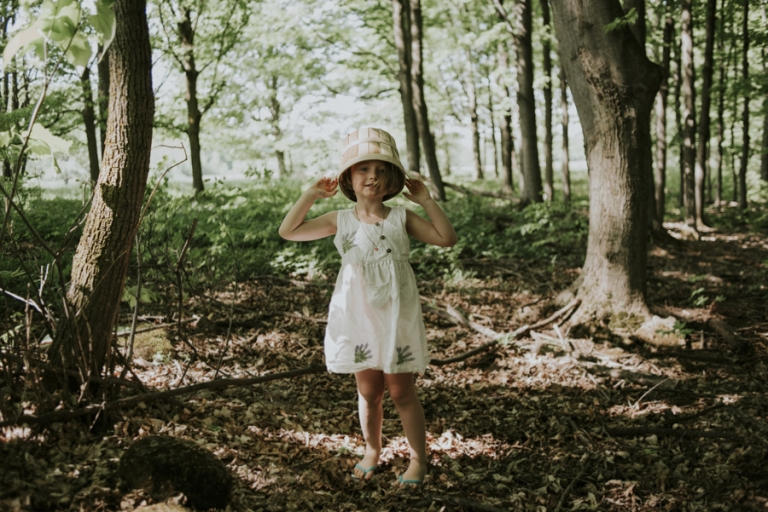 Girl in forest with bucket on head.