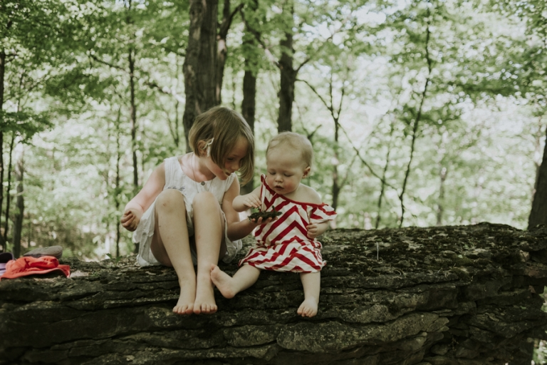 young sisters playing on stone.