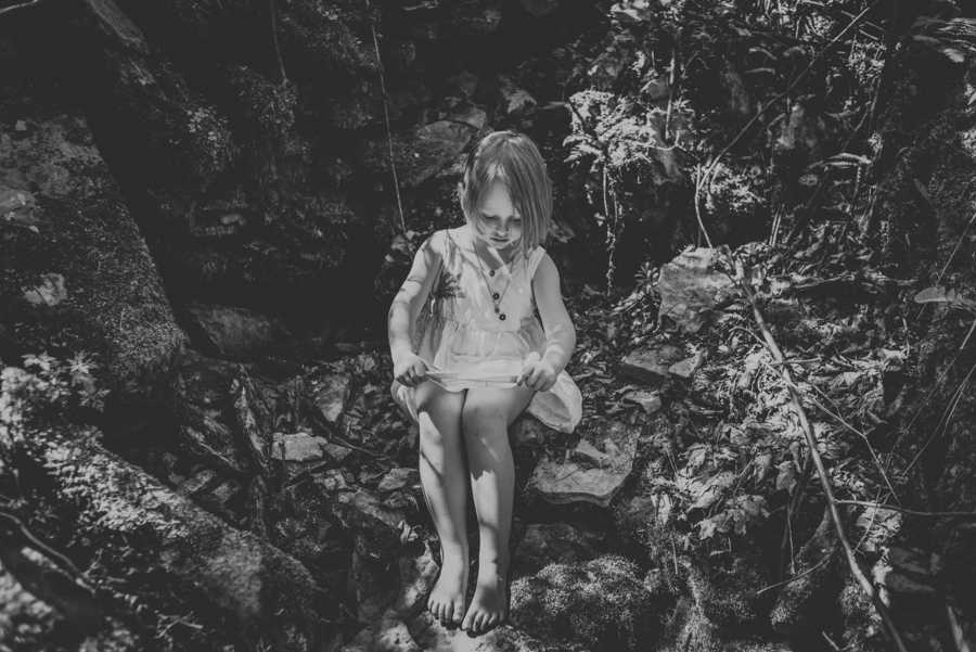 girl sitting on rock, back and white.