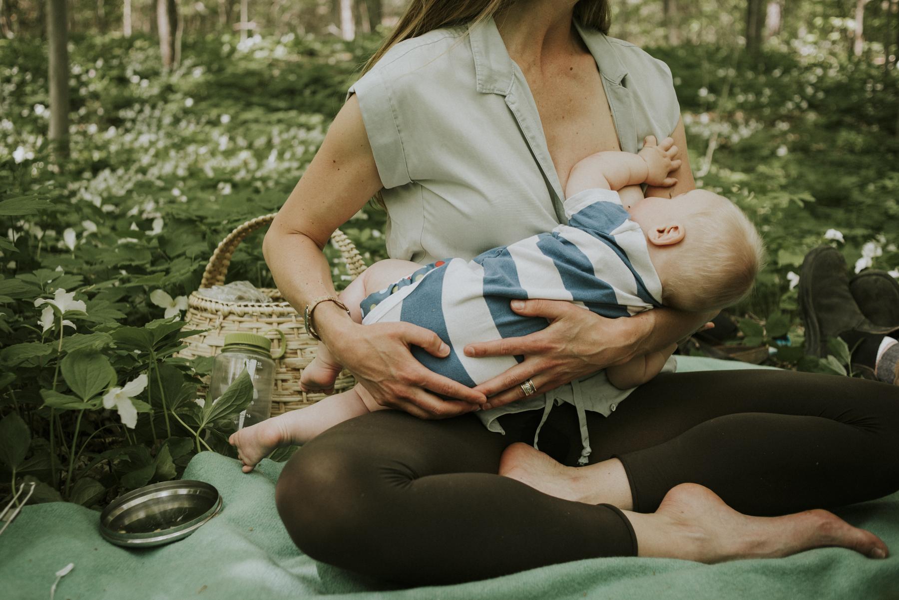 Mother nursing child in Thornbury forest, Ontario.