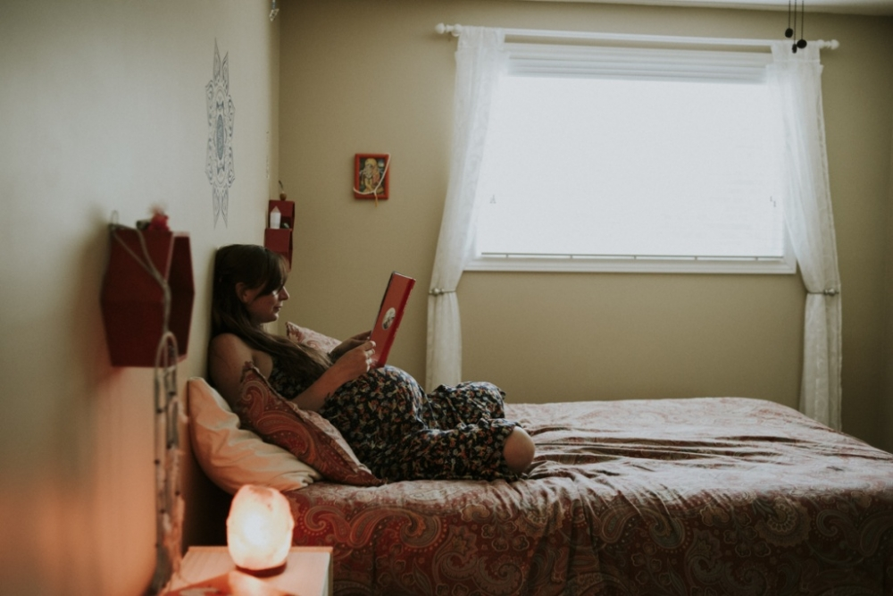 pregnant woman sitting on bed, ready book.