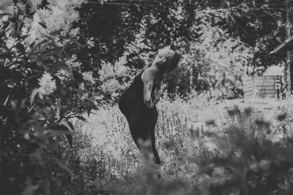 Pregnant Woman outside in the garden. Black and white. Yoga stretch.