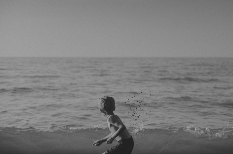 Boy throwing stones in water.