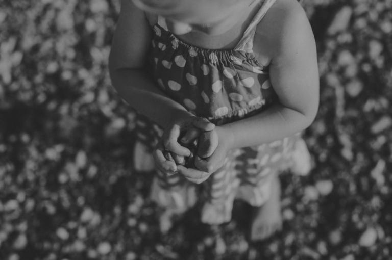 Little girl holding stones.