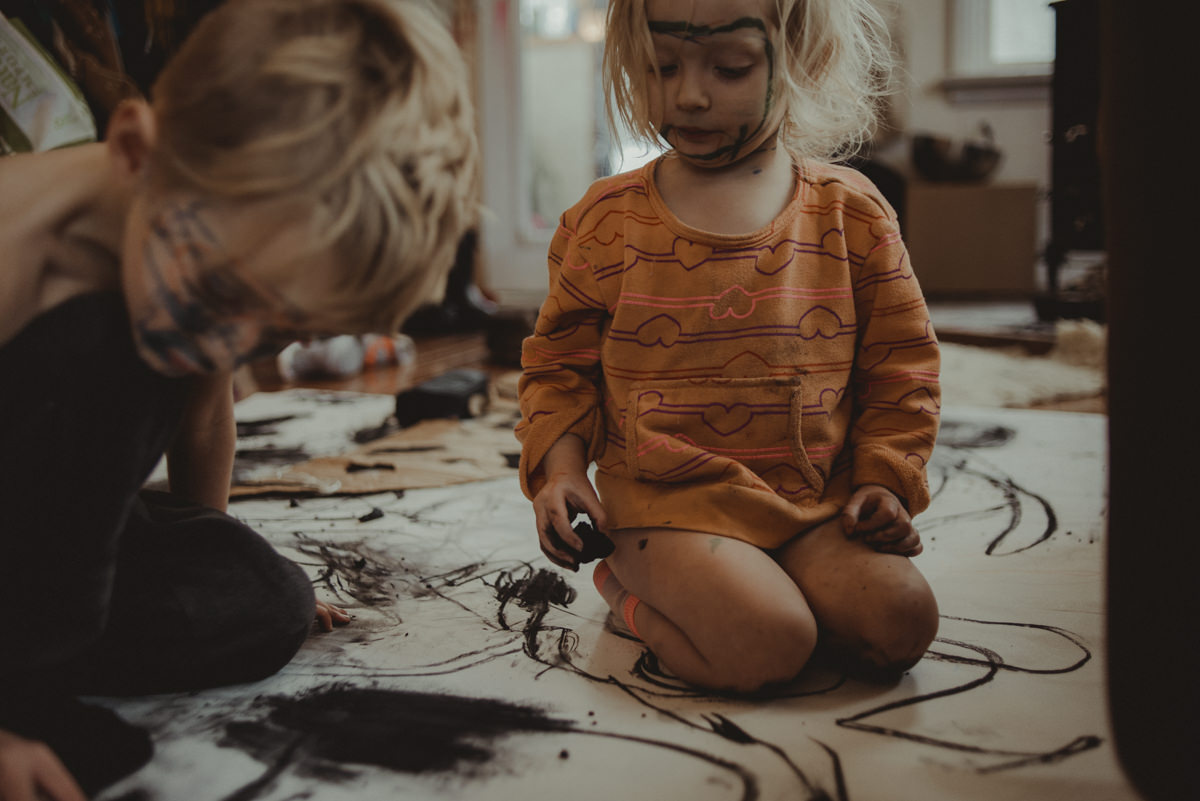 Free range kids playing with charcoal on the floor.