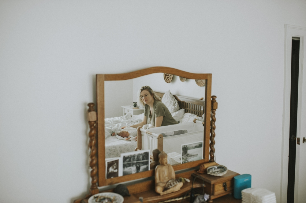 mom and newborn baby reflected in mirror.