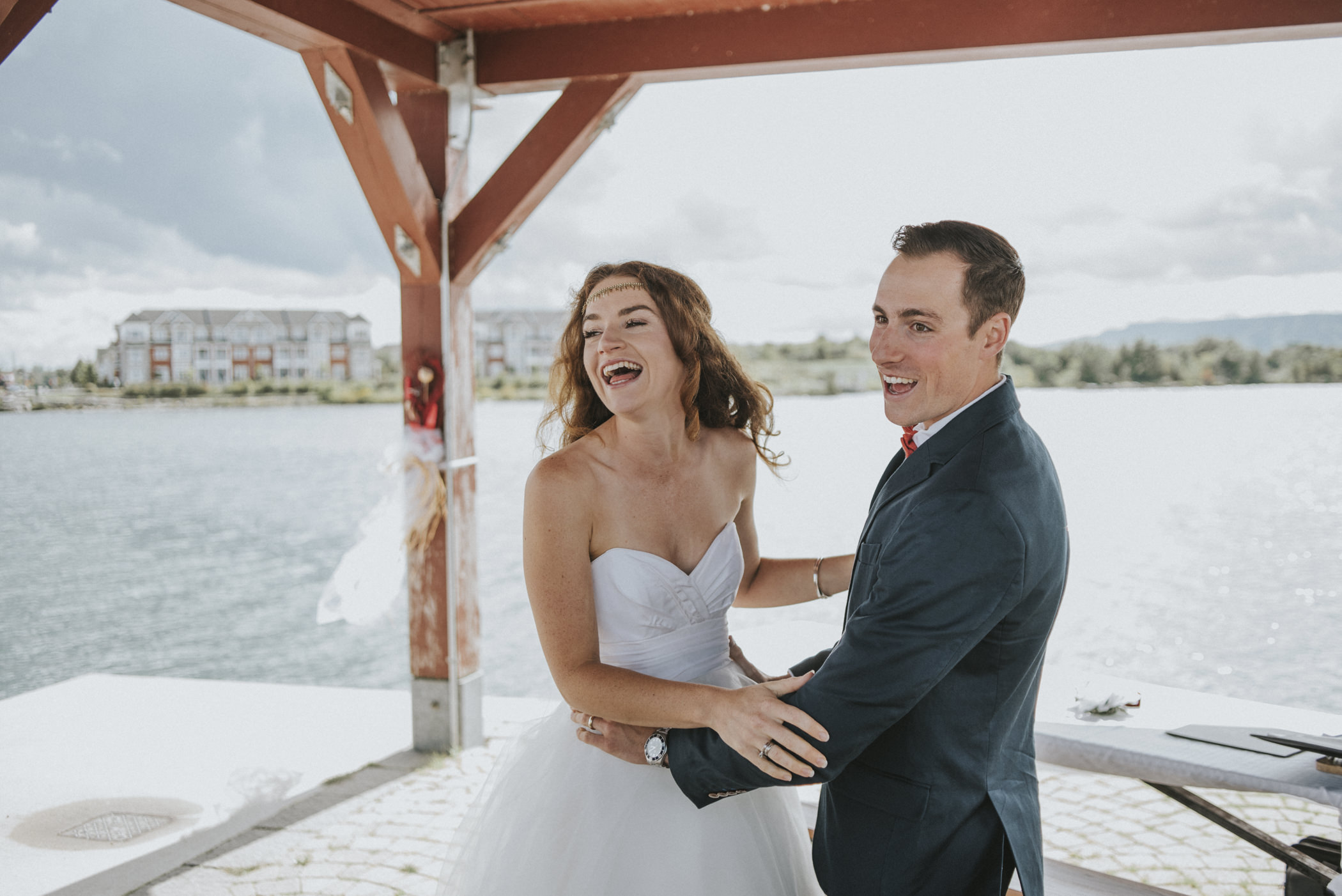 Bride and groom laughing after first kiss.