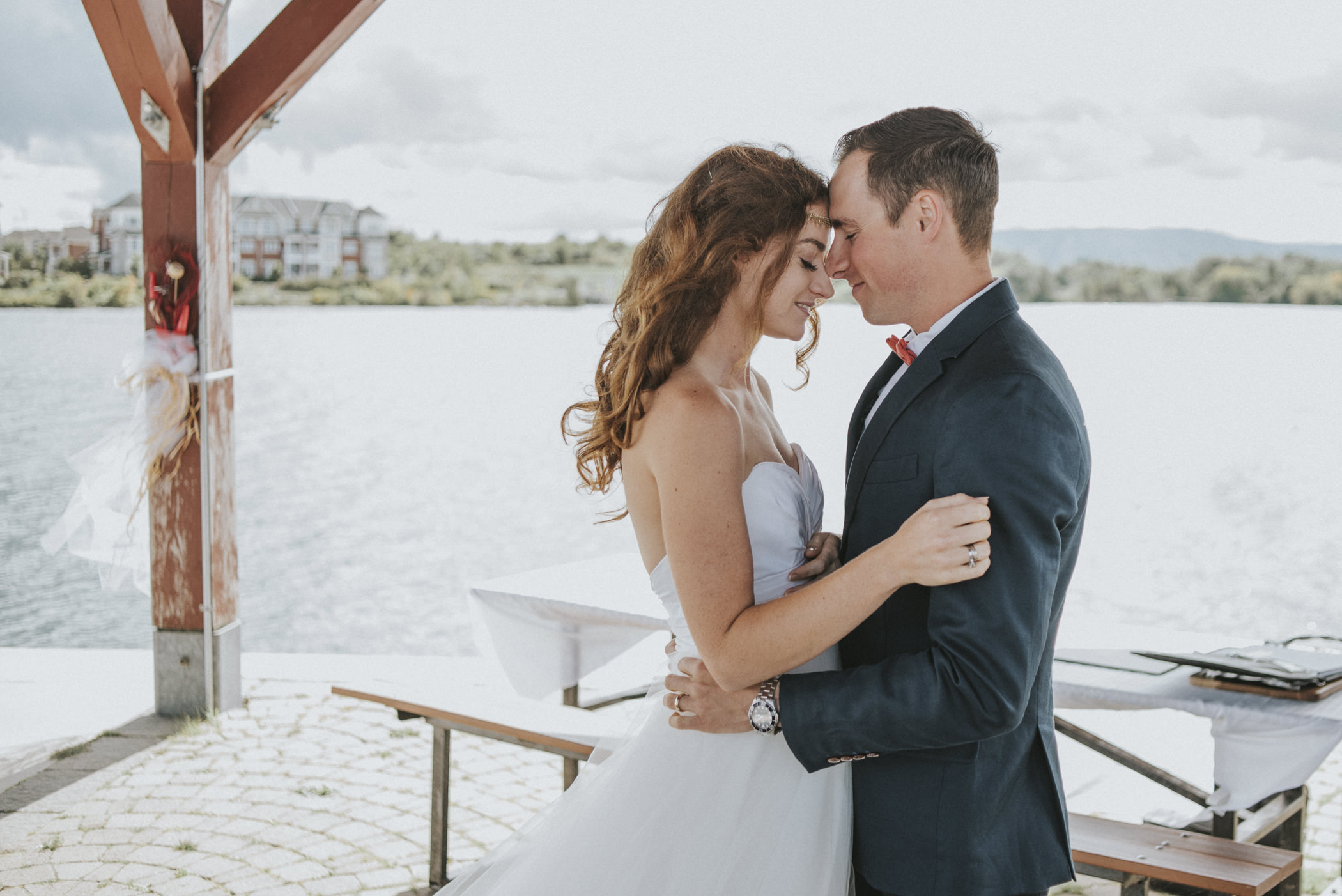 Bride and groom embracing after first kiss on pier.