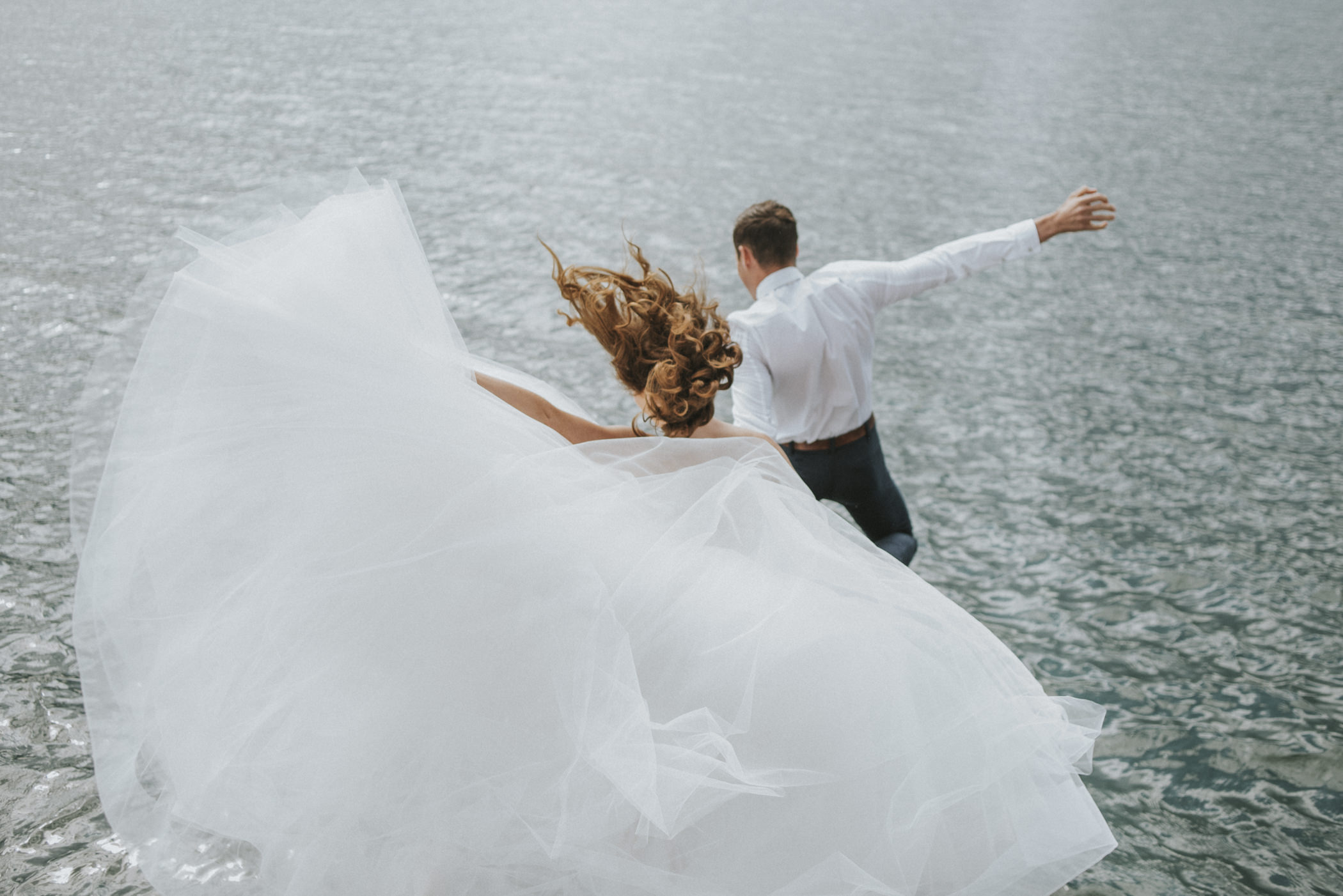 Bride and groom jumping off the pier into the water.