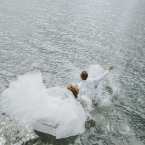 Bride and groom jumping into lake