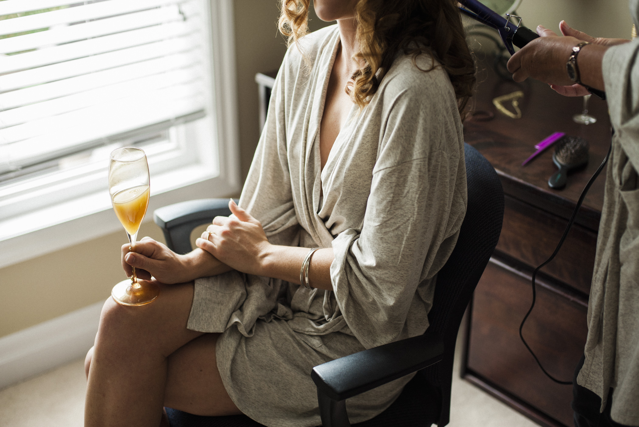 Bride drinking mimosa while getting hair done.