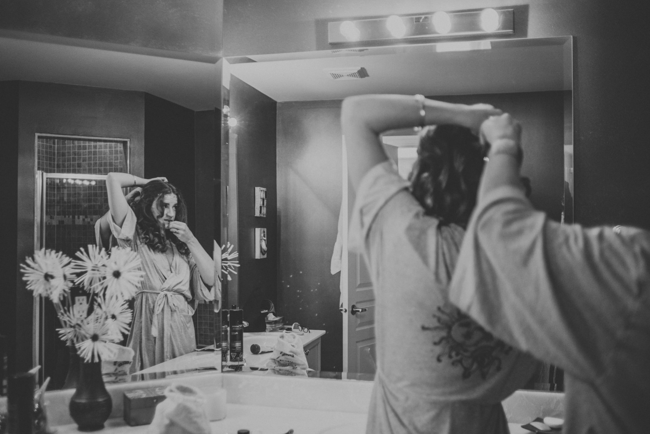 bride doing hair in bathroom with mirror reflection