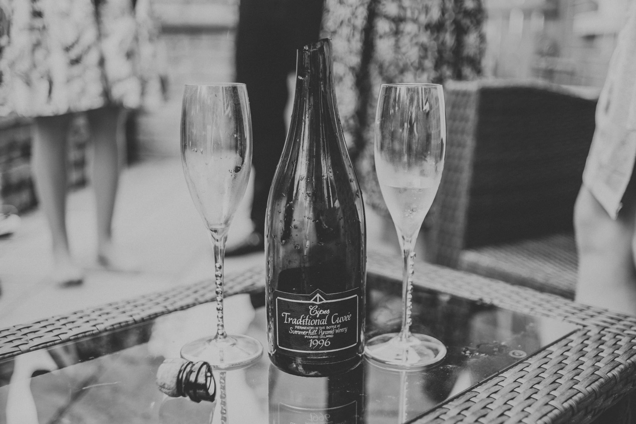 champagne bottle and glasses at backyard wedding