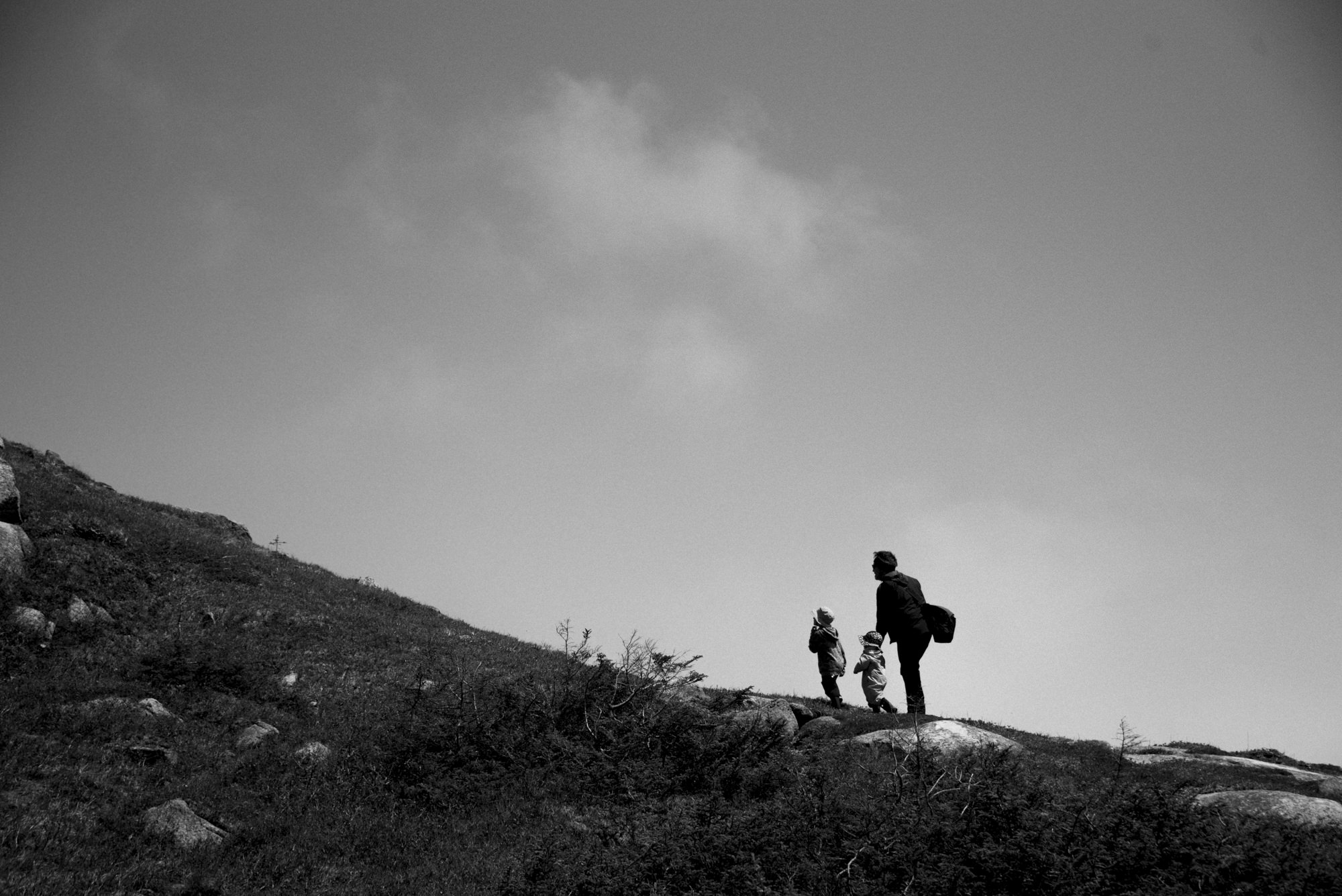 father and kids hiking up a hill