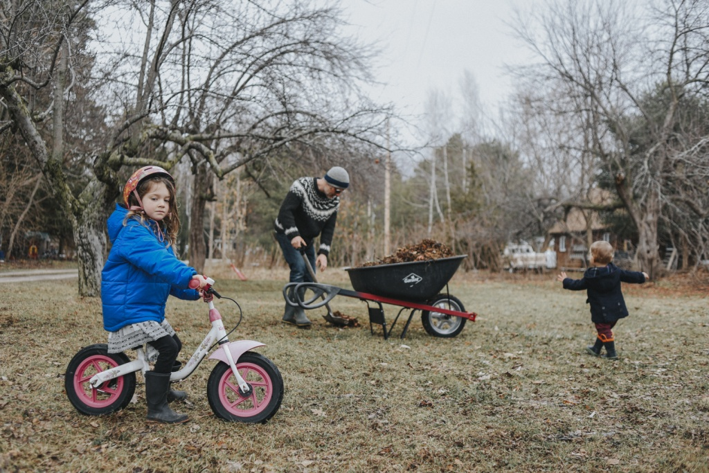 Family outside cleaning lawn. Child on bicycle.
