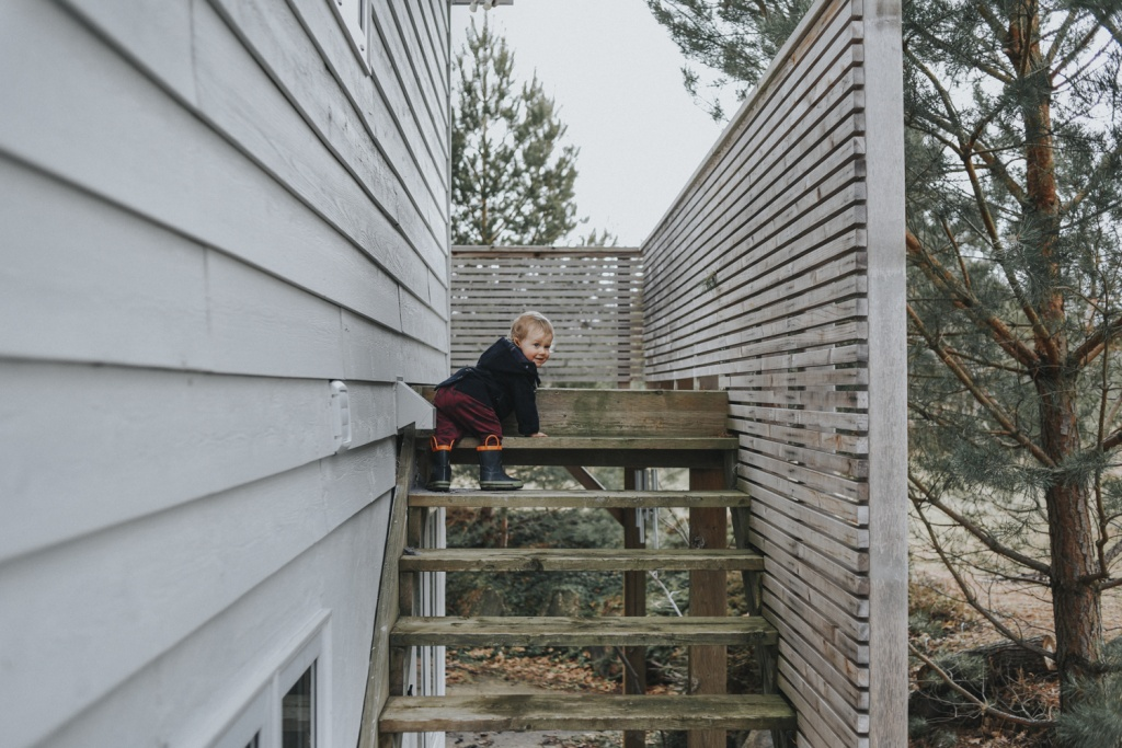 Toddler crawling up deck stairs.