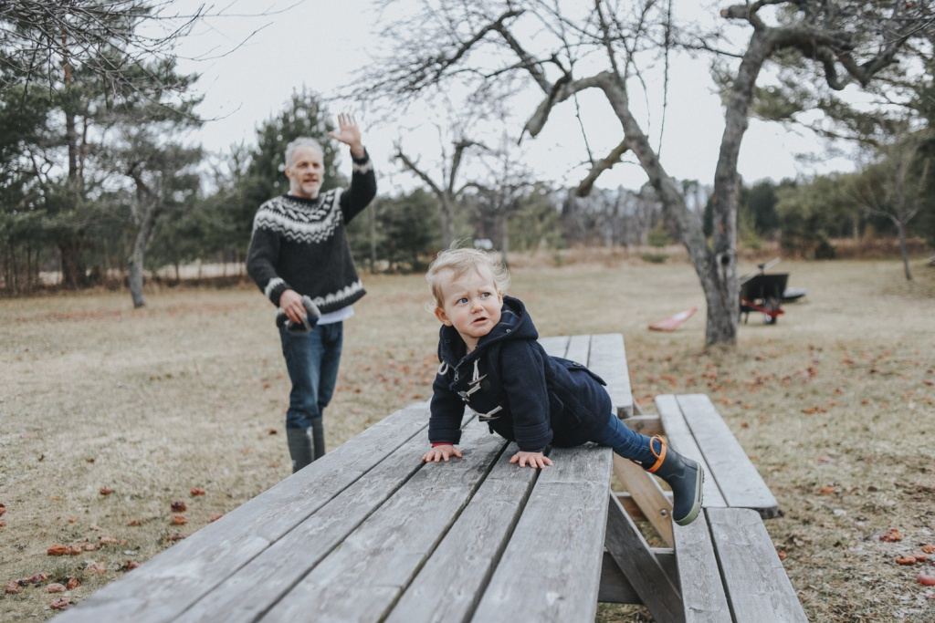 Father with son climbing on picnic table.