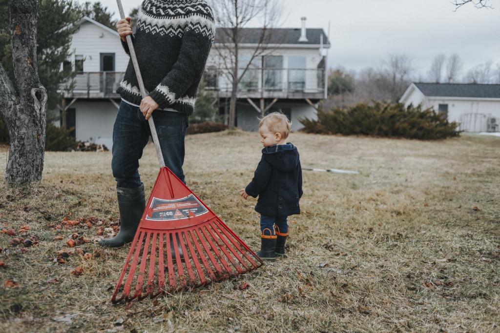 Boy watching father rake leaves.