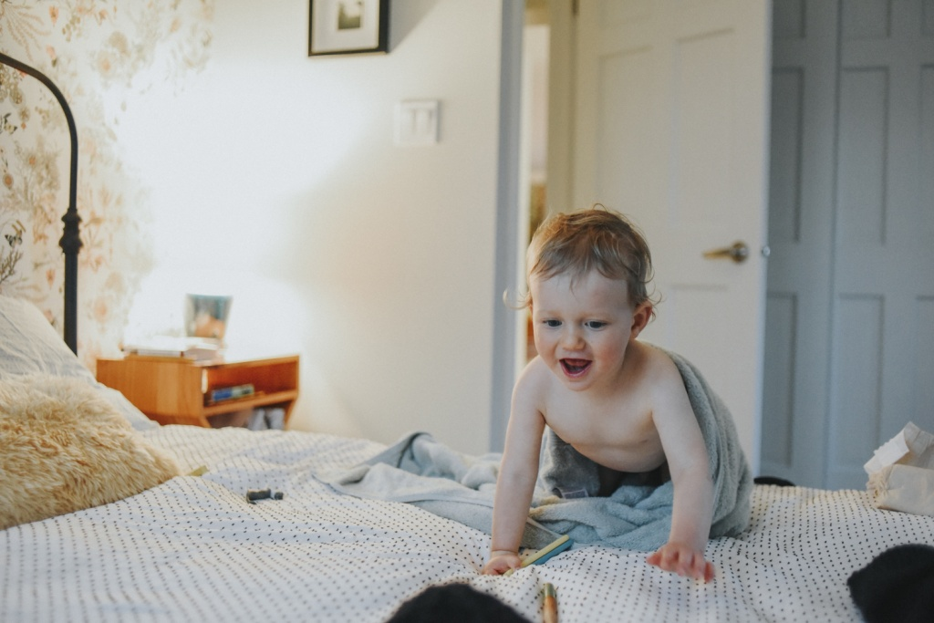 Toddler crawling on bed.