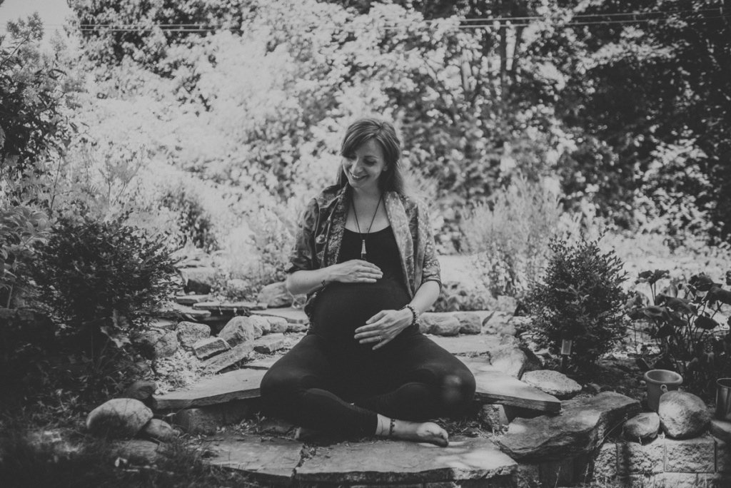 Pregnant Woman outside in the garden. Black and white. Sitting cross legged.