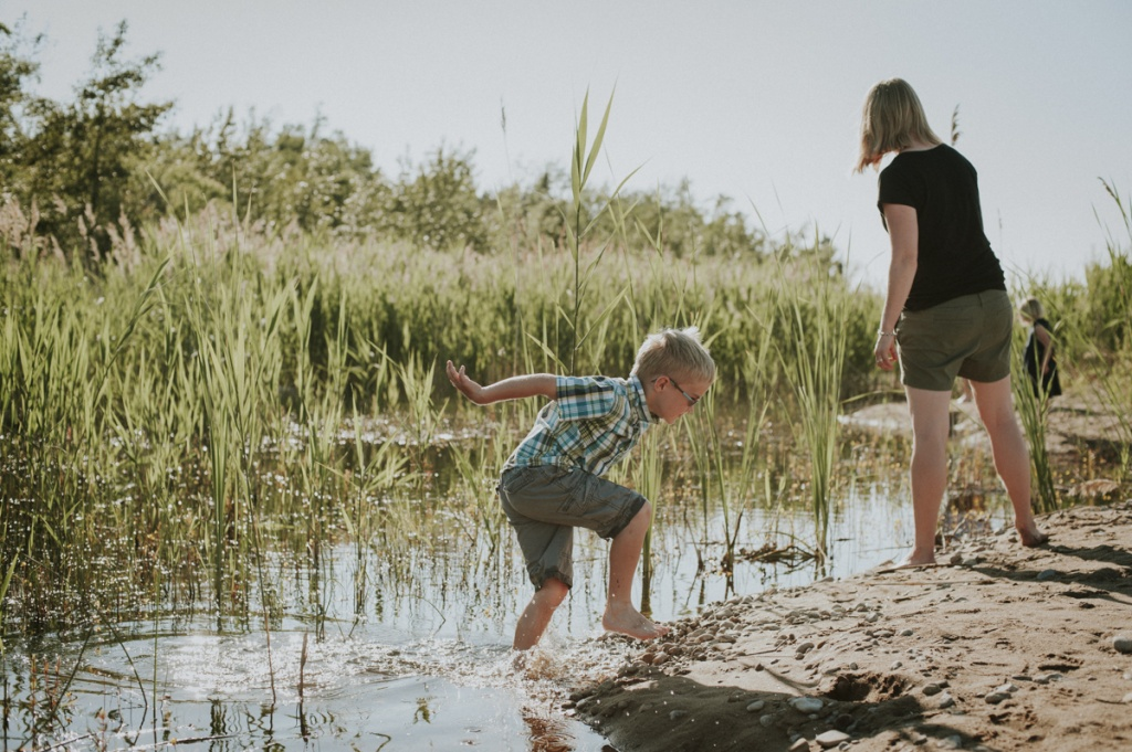 Child leaping out of pond. Family Photography by Sarah Tacoma.