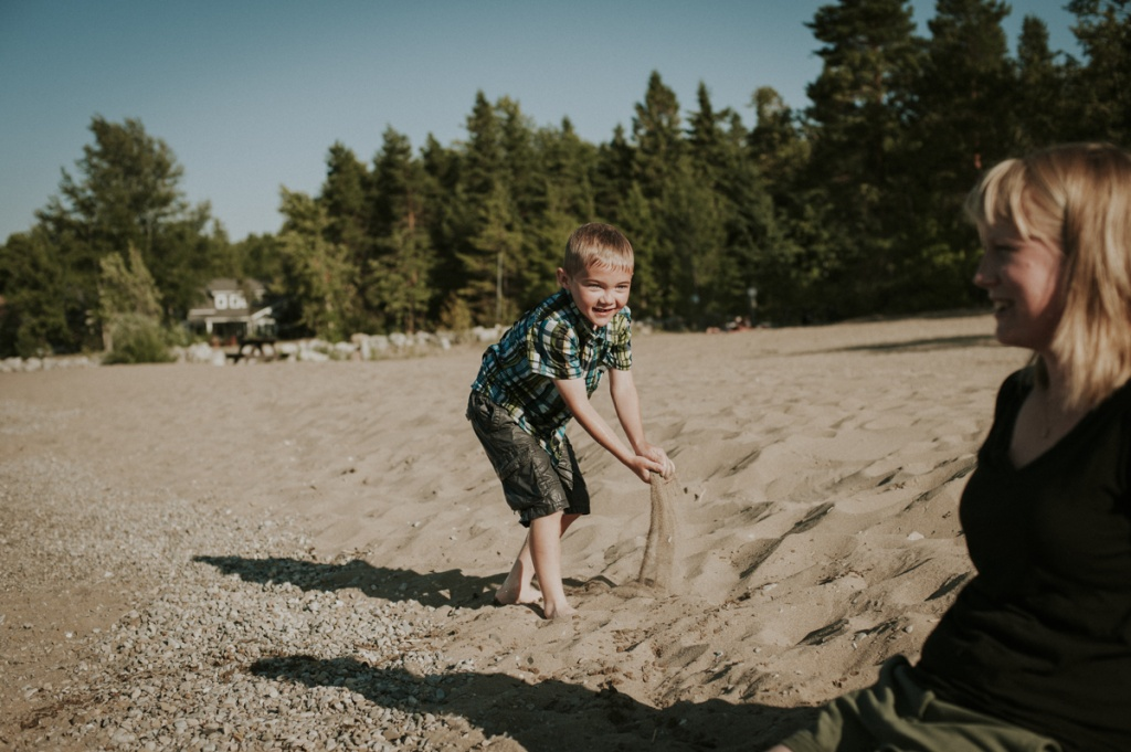 Child picking up sand. Family Photography by Sarah Tacoma.