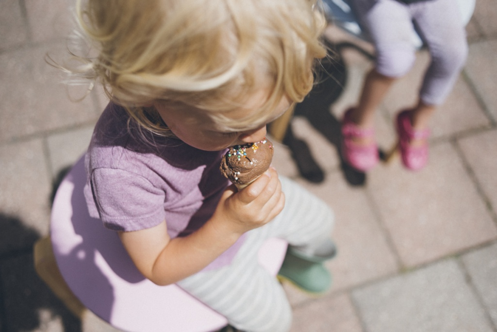 Kids eating ice-cream cones outside.