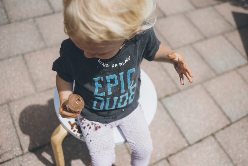 Child eating ice-cream cones outside.