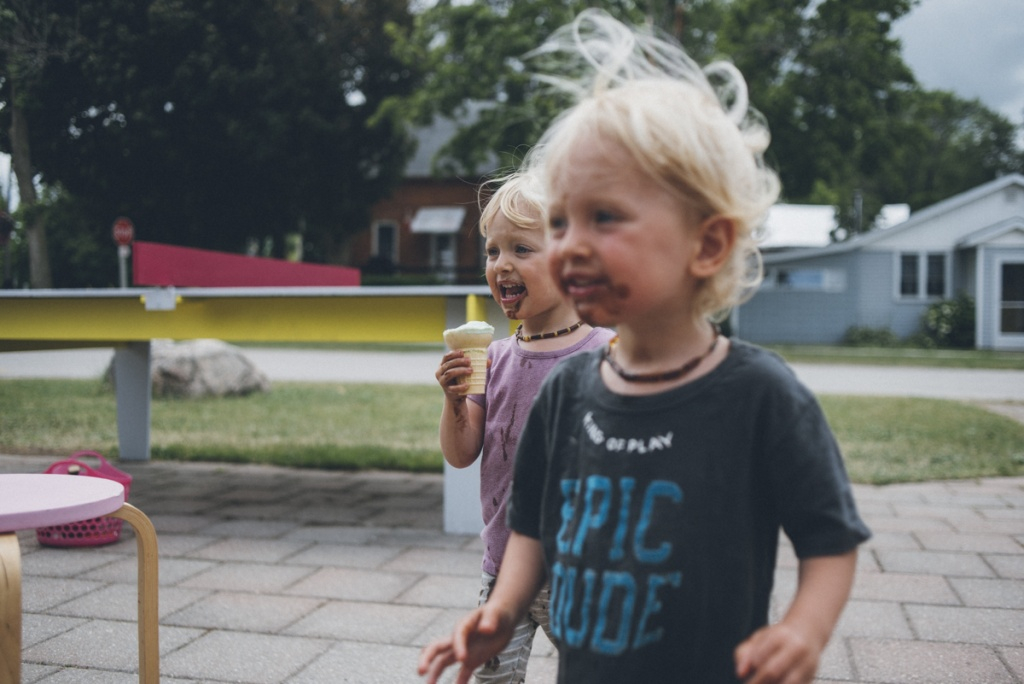 twin toddlers eating icecream on a windy day, hair blowing.
