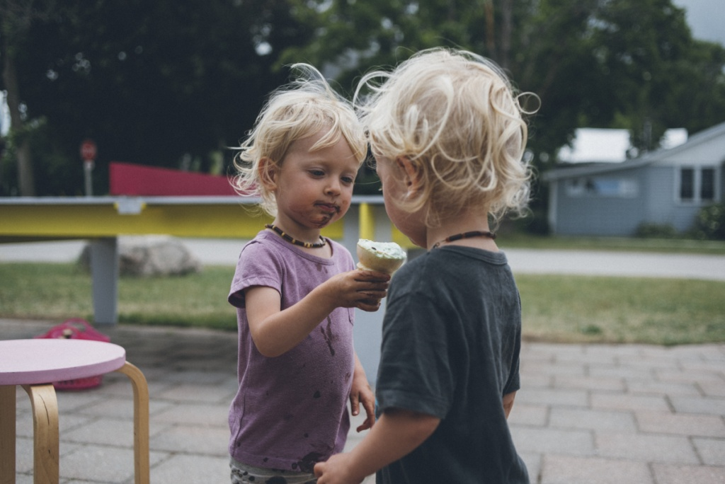twin toddlers sharing an ice-cream cone.
