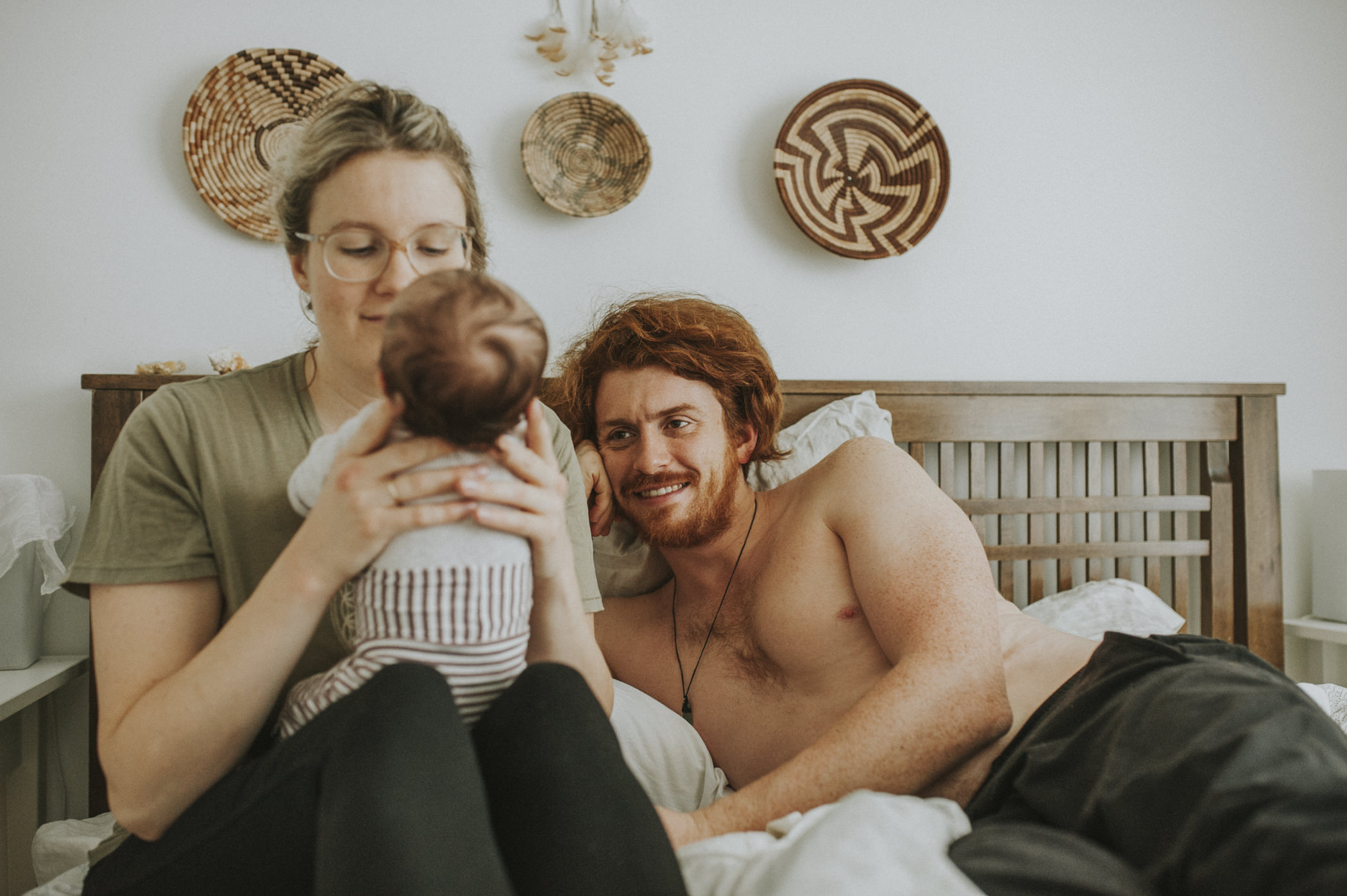 family on bed with newborn