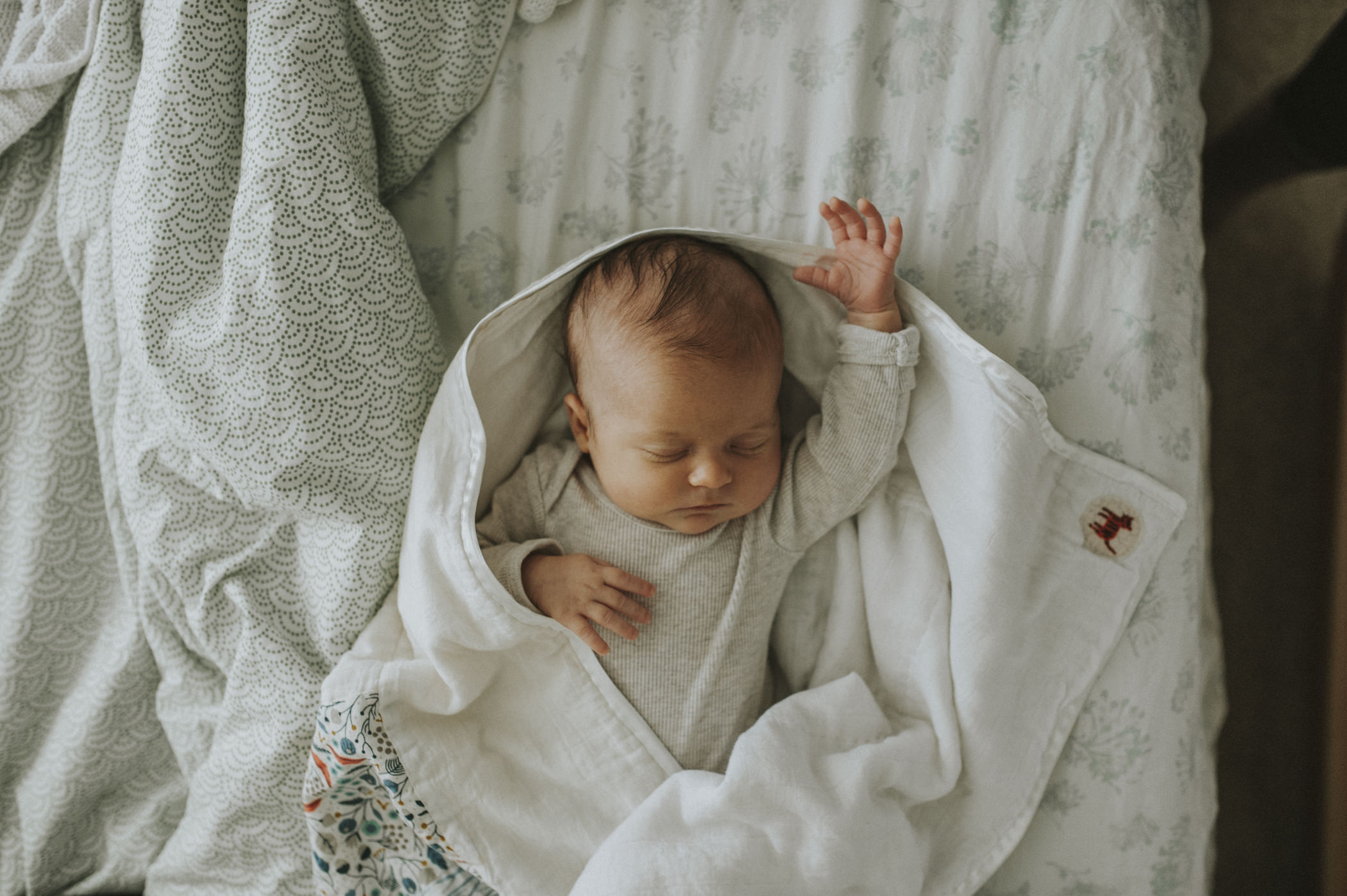 baby laying on bed in swaddle.