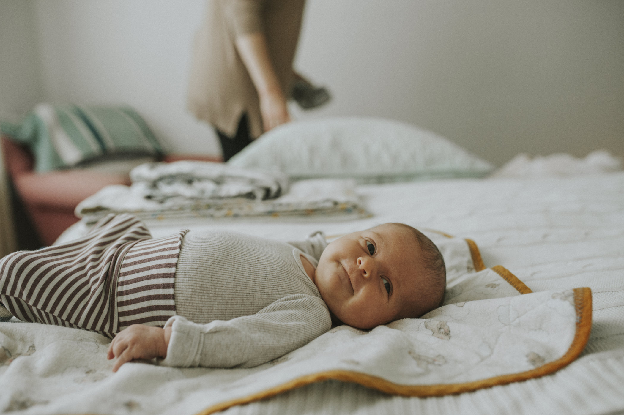 baby on bed, striped pants