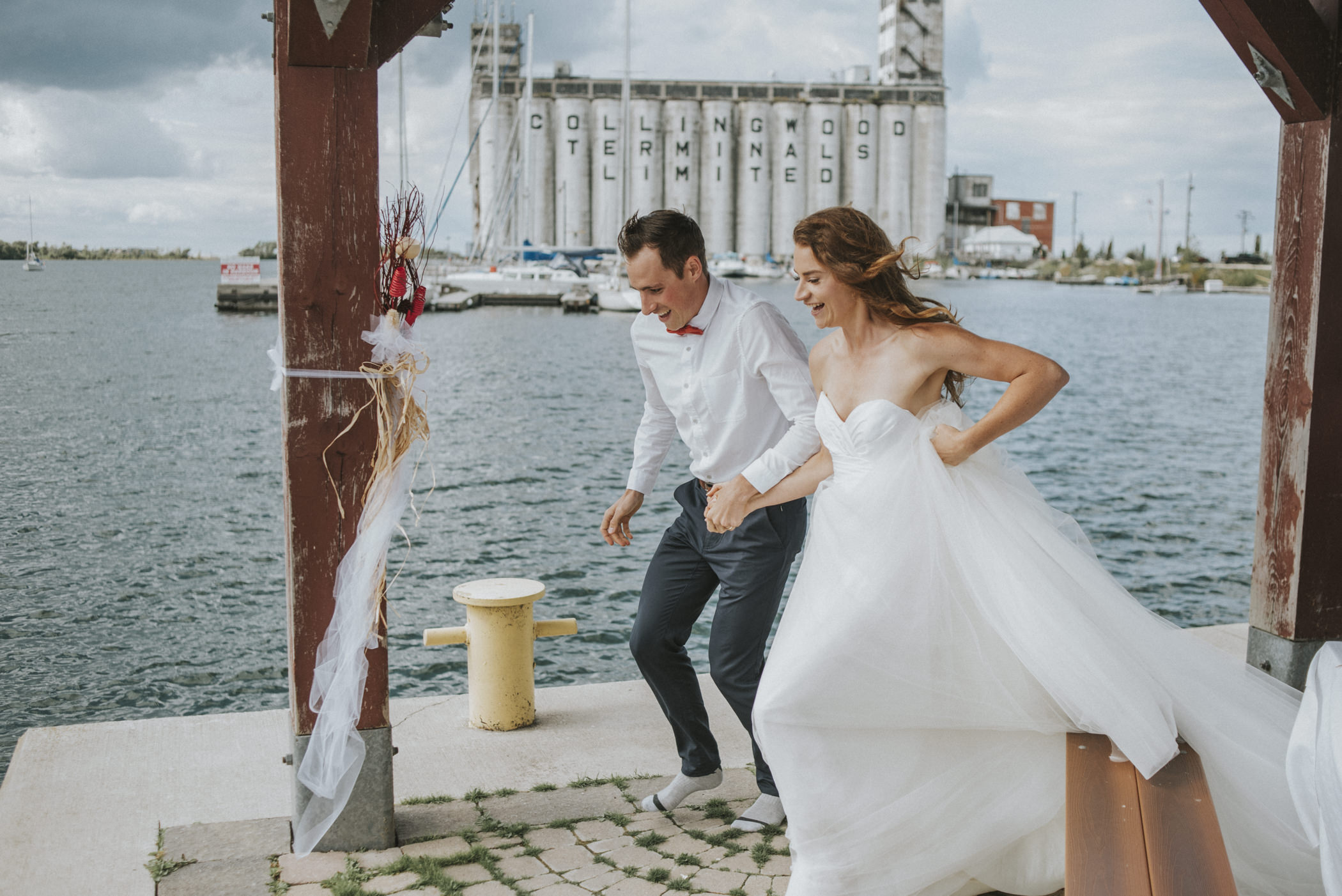 Bride and groom running down the pier / dock.