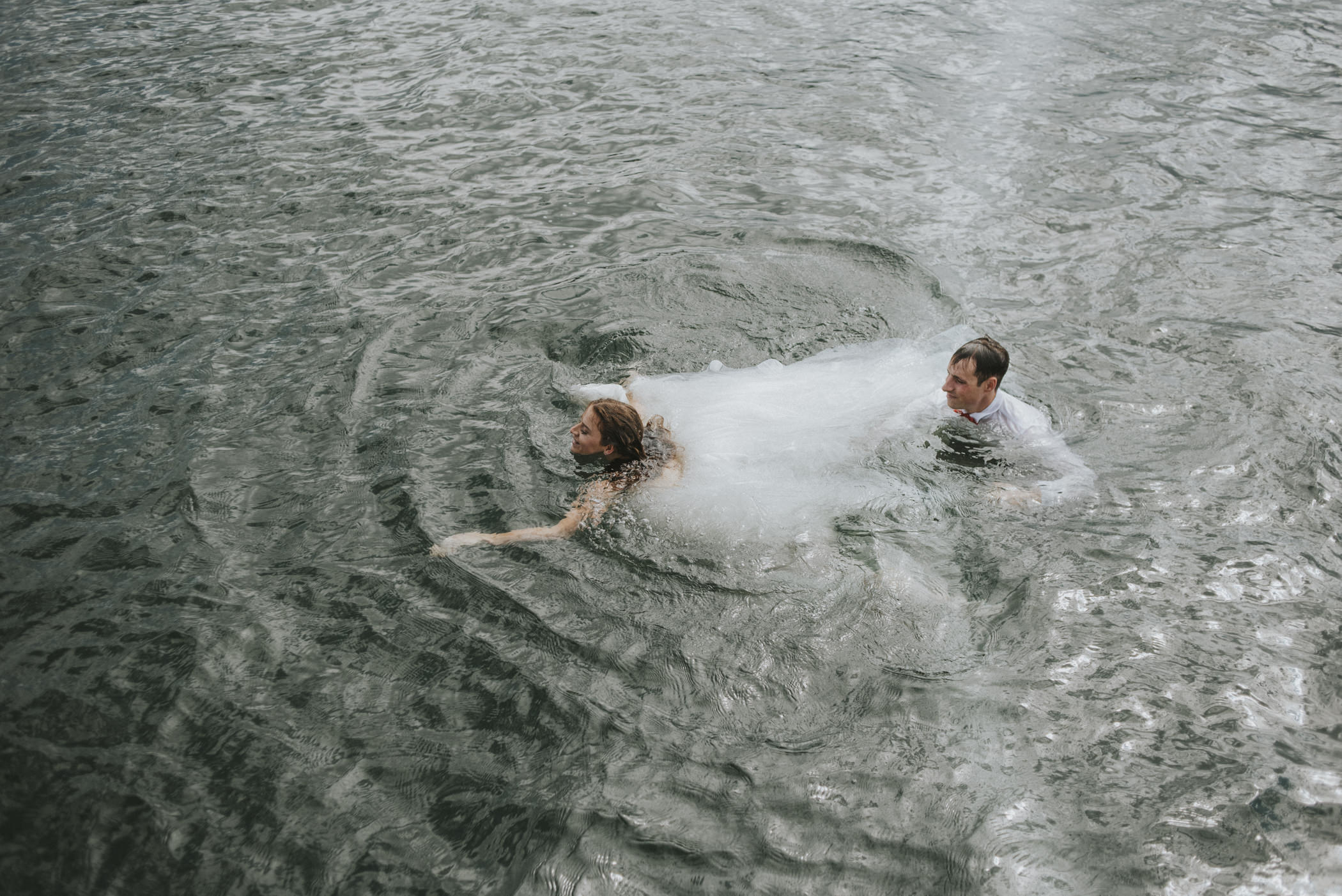 Bride and groom swimming in lake.