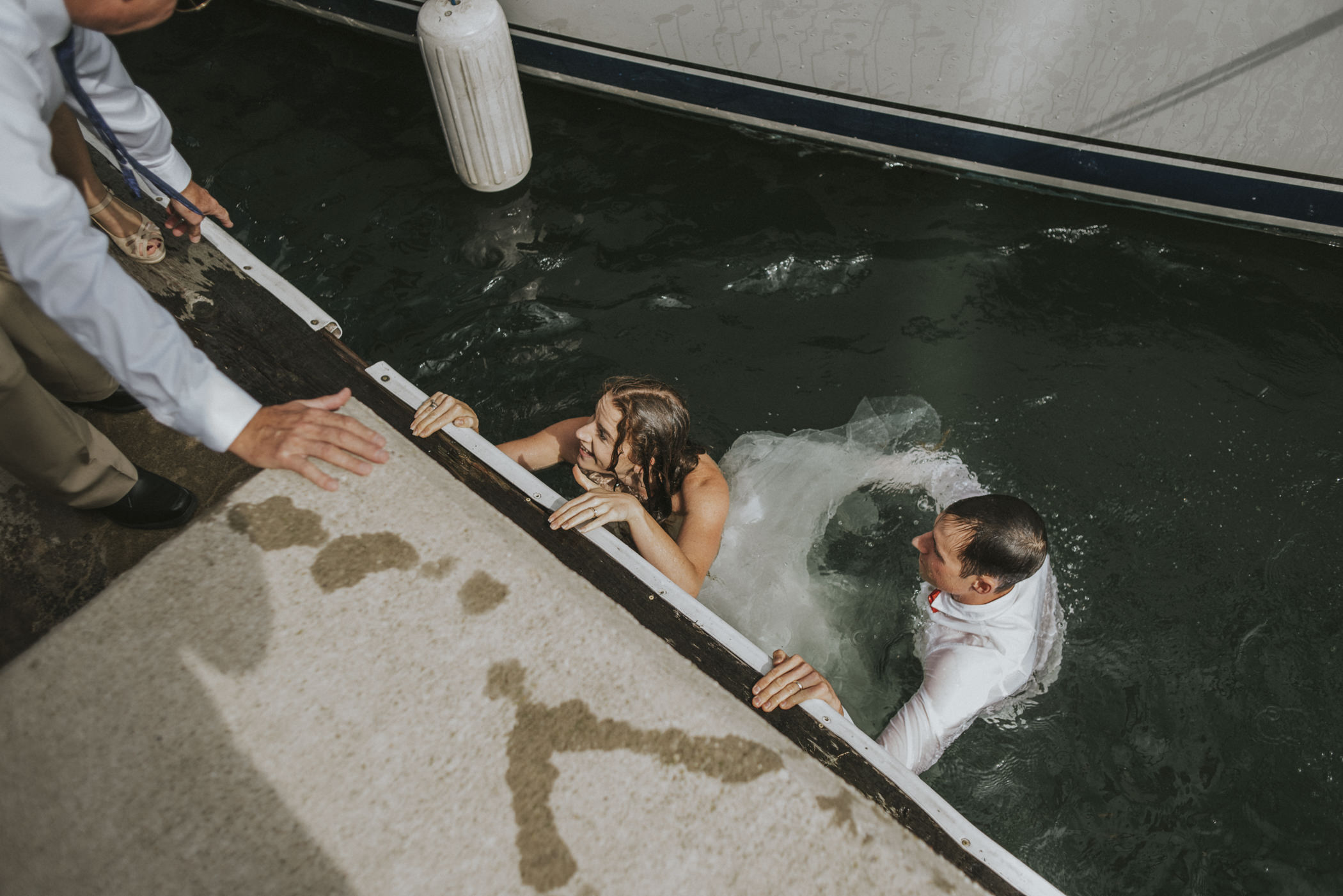 bride and groom climbing onto dock