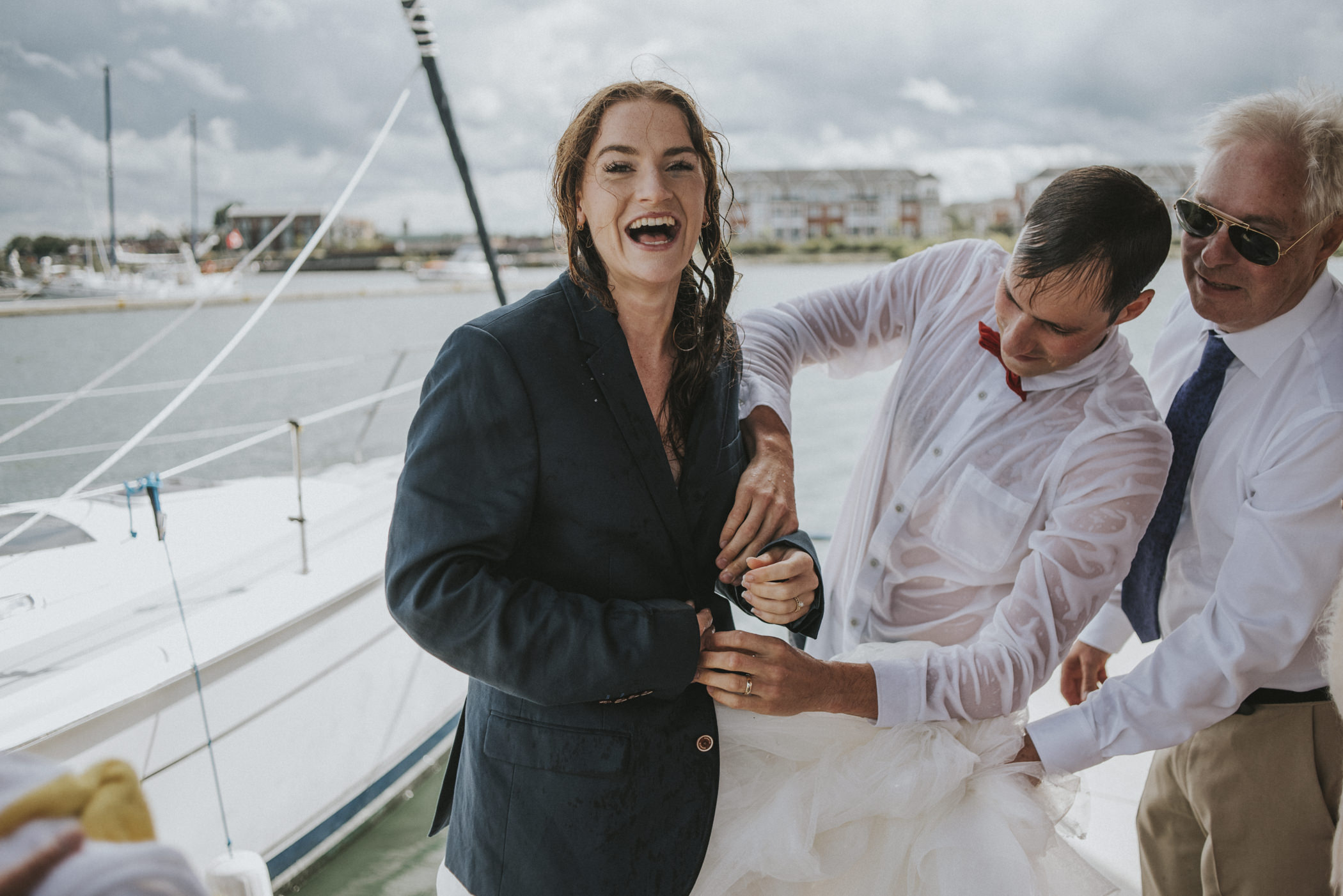 Groom putting suit jacket on soaked bride.