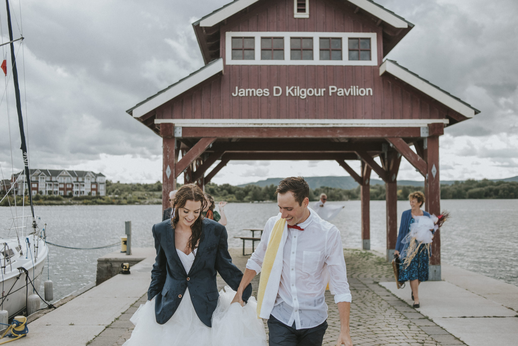 bride and groom walking down dock after swimming.
