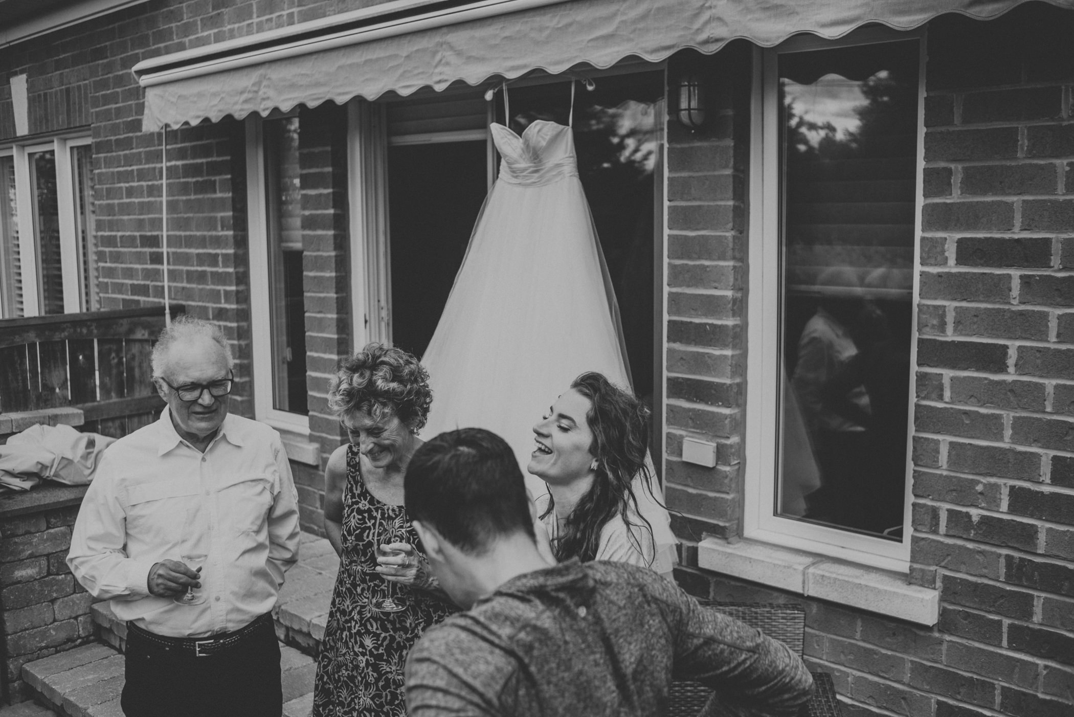 friends and family at backyard wedding, bride laughing with wet dress hanging.