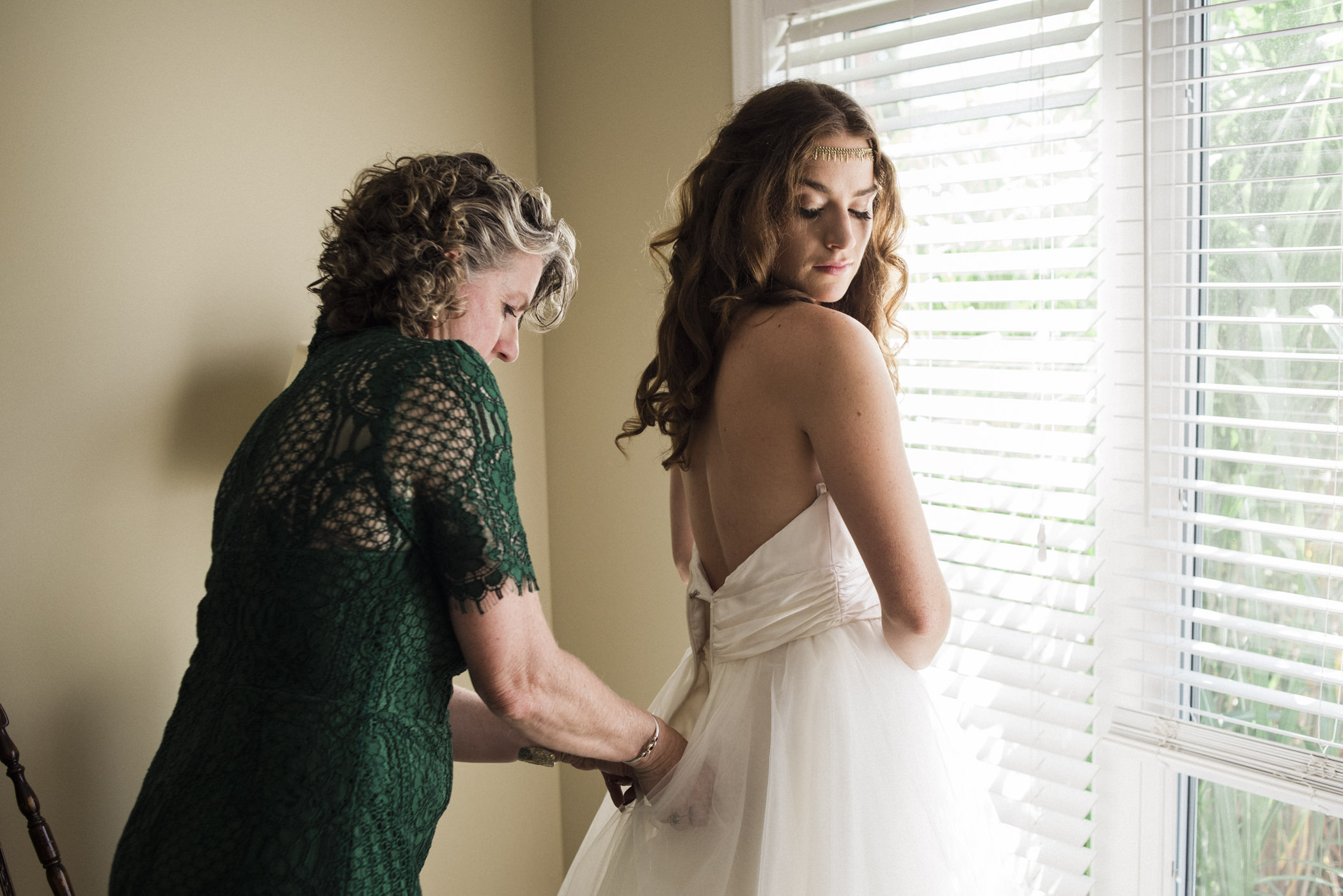 bride's mother helping her into her dress
