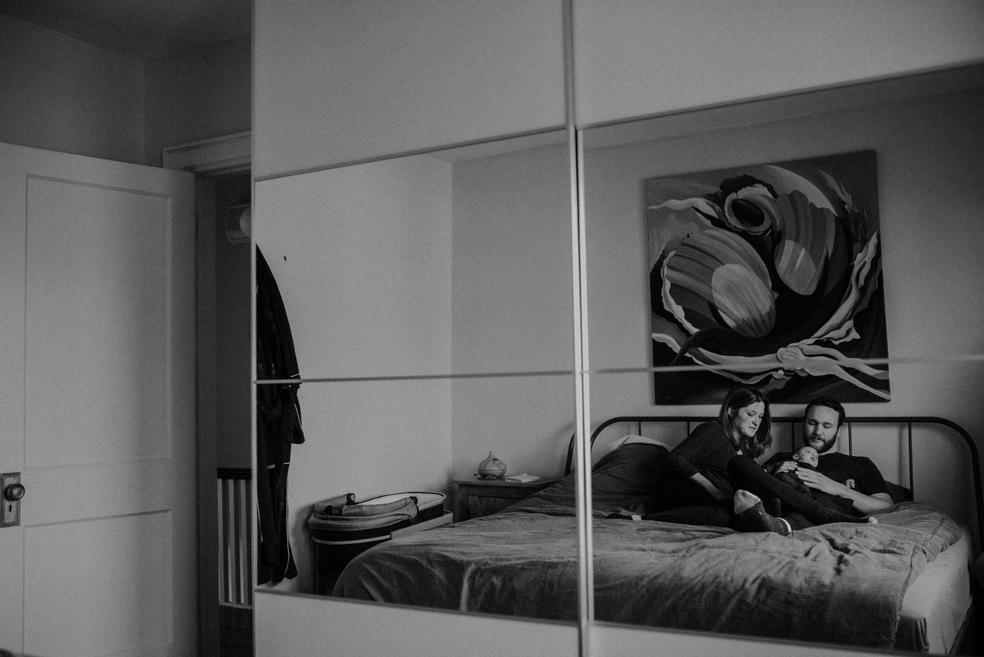 newborn family session, toronto. Reflection in mirror of family in bed.
